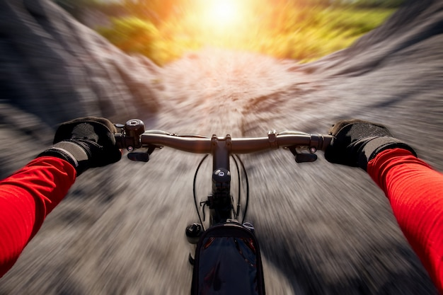 Cyclist riding mountain bike on the rocky trail at sunset. Premium Photo