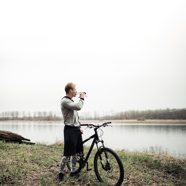 Cyclist standing with bicycle looking at lake while drinking water from bottle Free Photo