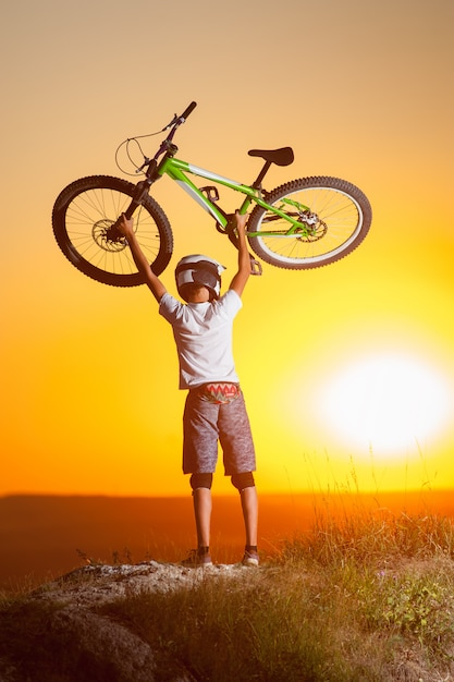 Cyclist with mountain bike on the hill in the evening Premium Photo