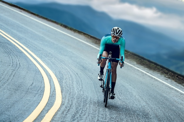Cyclists are cycling, climbing up to the top. Premium Photo