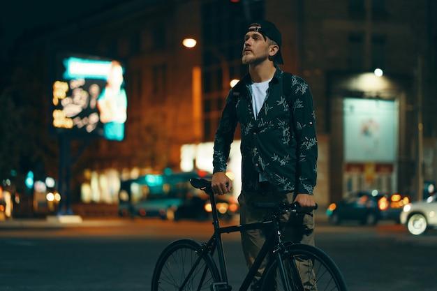 Велосипедисты, стоящие на дороге в сторону своего классического велосипеда, пока смотрят Бесплатные Фотографии