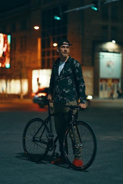 Велосипедисты стоят на дороге в сторону своего классического велосипеда, наблюдая за ночным городом Бесплатные Фотографии