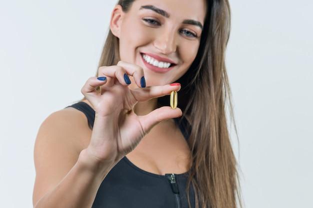 Молодая здоровая женщина в спортивной одежде с витамином d, e, a, рыбий жир, капсулы омега-3 Premium Фотографии