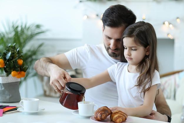 お父さんと娘が台所で朝食をとり 無料写真