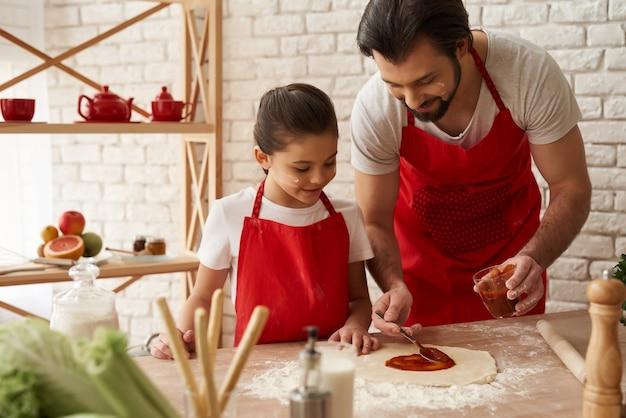 Папа и дочь готовят пиццу с томатным соусом. Premium Фотографии
