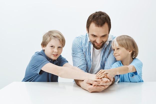 お父さんと息子は家族だけでなくチームです。幸せそうに見える兄弟とテーブルに座って手を繋いでいる父親の肖像画 無料写真