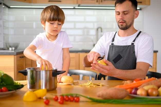 Free Photo | Dad and child peeling veggies