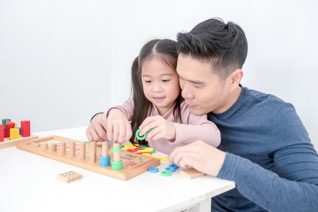 Dad and daughter are playing toys together fun, dad is teaching daughter to block toys. Premium Photo