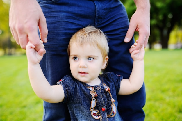 Dad holds baby daughter's hands on the background of trees. dad and daughter relaxing in the park grass ene Premium Photo