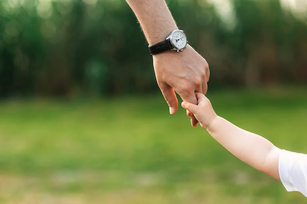 The dad holds the child by the hand Premium Photo