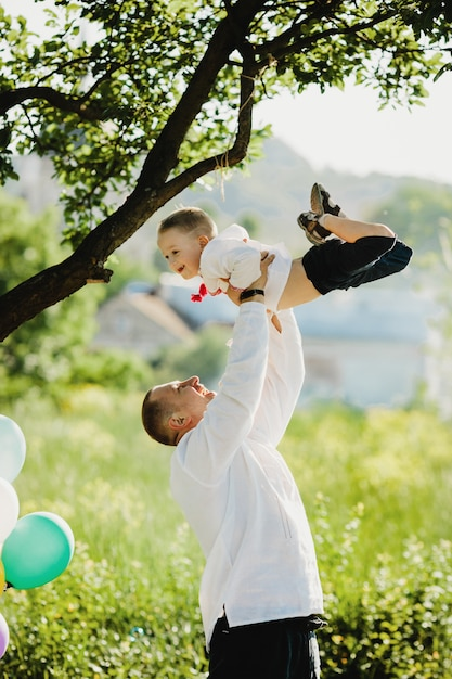 Dad holds little son in embroidered shirt in his arms standing under green tree Free Photo