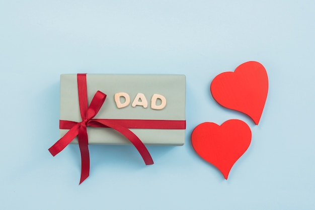 Dad inscription with gift box and hearts Free Photo
