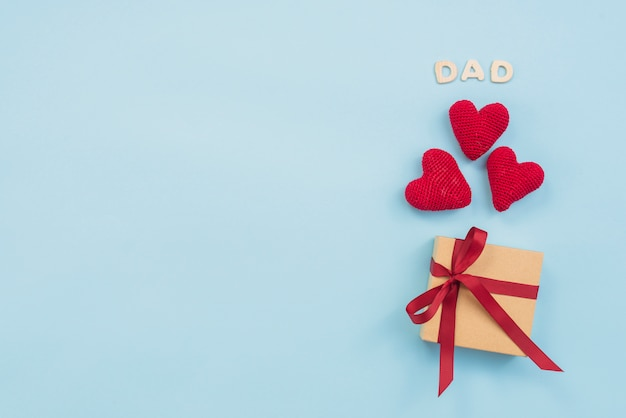 Dad inscription with gift box and toy hearts Free Photo