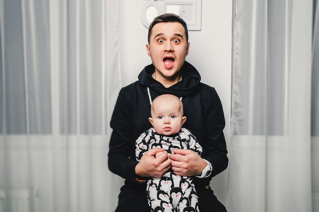 Dad and little baby show different emotions in the camera Premium Photo