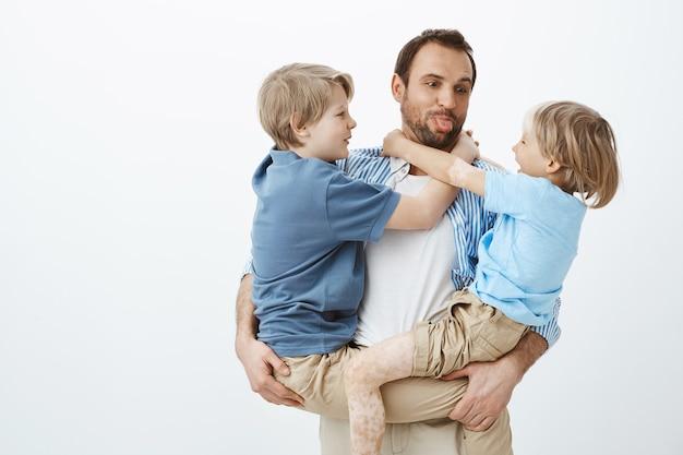 Папа любит проводить время с семьей. беззаботный счастливый отец держит сыновей на руках и высунул язык Бесплатные Фотографии