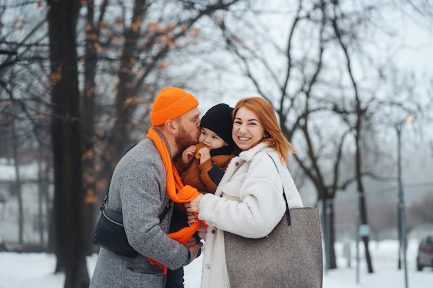 Dad mom and baby in the park in winter Free Photo