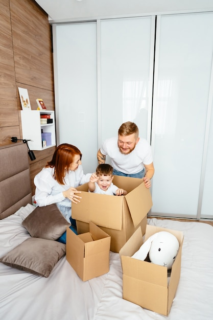 Dad, mom and little son play in the bedroom with paper boxes Free Photo