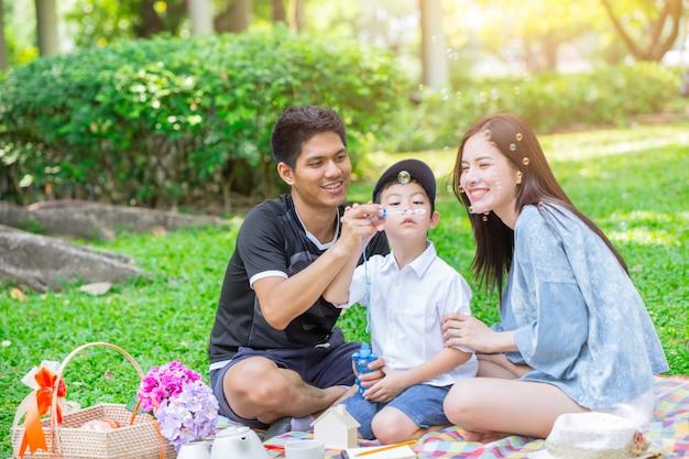 Dad mom and son enjoy picnic family day holiday at green park Premium Photo