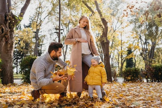 Papà e madre con bambino all'aperto Foto Gratuite