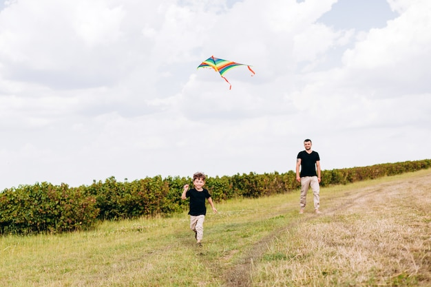 Dad and son having a funny time,launch a kite on nature Premium Photo
