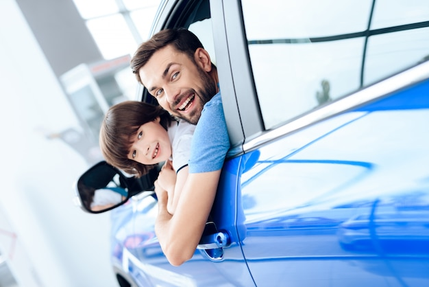 Dad and son look out of the window of a newly purchased car. Premium Photo