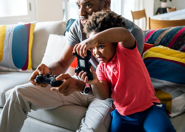 Dad and son playing game at living room together Free Photo