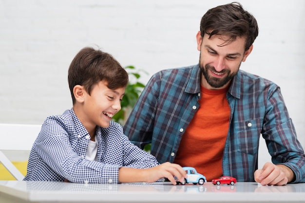 Dad and son playing with toy cars Free Photo