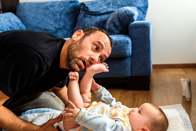 Dad struggling with his baby daughter to change dirty diapers putting faces of effort, concept of fatherhood. Premium Photo