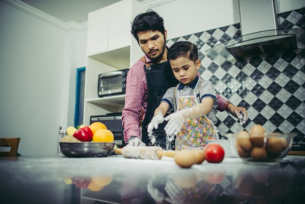 Dad teach his son how to cook in kitchen at home. family concept. Free Photo