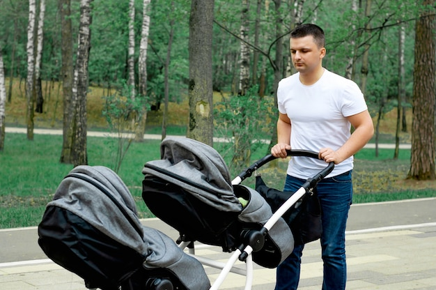 Dad walks in the park with two young children Premium Photo