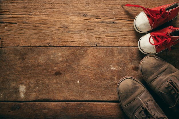 Daddy's boots and baby's shoes, fathers day concept Premium Photo