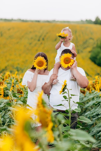 Папа несет на плечах маленькую дочку в поле цветов. концепция летнего отдыха. день отца, матери, ребенка. проводить время вместе. выборочный фокус Premium Фотографии