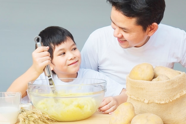 Daddy and son making mashed potatoes happily Free Photo