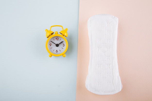 Daily pad and yellow alarm clock on blue pink background. female's menstrual cycle concept. Premium Photo