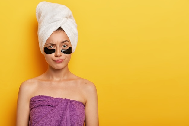 Daily pampering routine. lovely young female model wears under eye circles for removing dark circles, takes care of her skin, uses modern cosmetics Free Photo