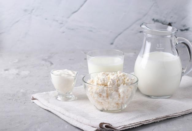 乳製品:牛乳、ケフィアまたはアイラン、カッテージチーズ、サワークリーム、透明なボウル、水差し、灰色の表面のガラス、テキスト用のスペース、クローズアップ Premium写真