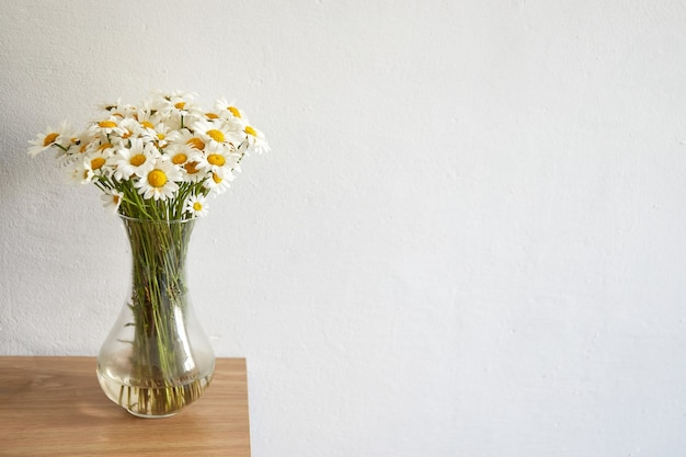 Daisy flowers bouquet in glass vase staying on wooden board. home interior. Premium Photo