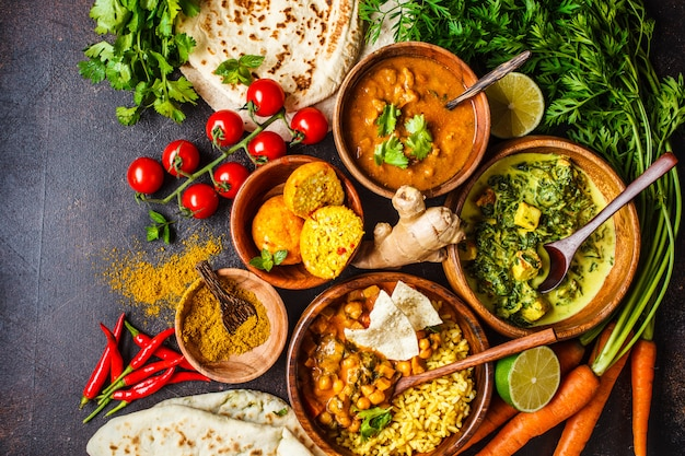 Dal, palak paneer, curry, rice, chapati, chutney in wooden bowls on dark table. Premium Photo