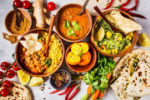 Dal, palak paneer, curry, rice, chapati, chutney in wooden bowls on white table. Premium Photo