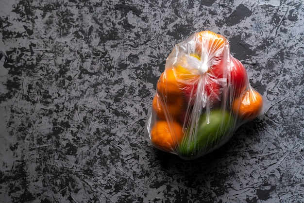 Damaged spoiled fruits in a bag in a dark room, plastic container harm Premium Photo