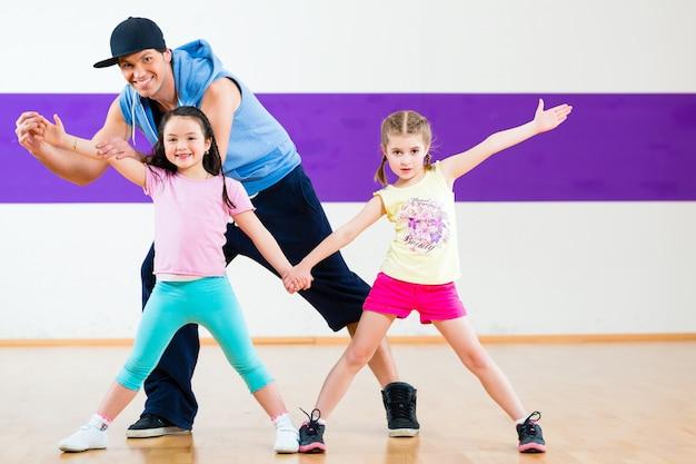 Dance teacher giving kids zumba dancing class Premium Photo