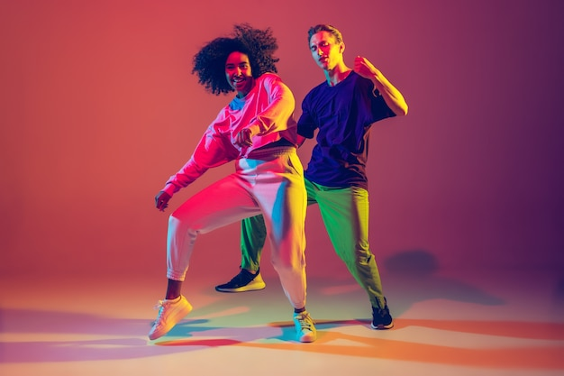Dance time. stylish men and woman dancing hip-hop in bright clothes on green background at dance hall in neon light. Free Photo