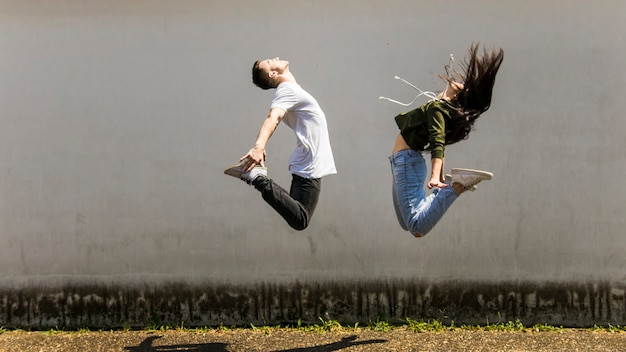 Dancer jumping in air against gray wall Free Photo
