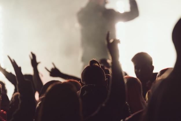Танцы на концерте во время выступления певца в окружении огней Бесплатные Фотографии
