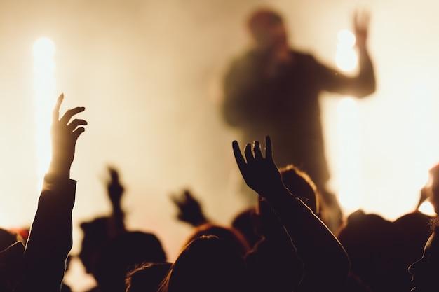 콘서트에서 춤을 추는 동안 가수가 조명에 둘러싸여 공연을합니다. 무료 사진