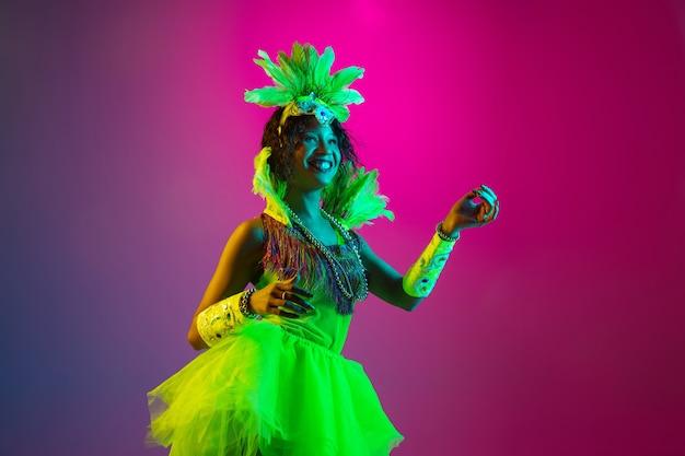 댄스. 네온 그라데이션 벽에 춤 깃털을 가진 카니발, 세련 된 무도회 의상에서 아름 다운 젊은 여자. 휴일 축하, 축제 시간, 댄스, 파티, 재미의 개념. 무료 사진