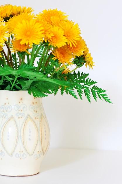 Dandelions in a clay vase Premium Photo
