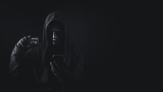 クレジットカードを保持しているフード付きの使用スマートフォンの危険な匿名のハッカー男 Premium写真