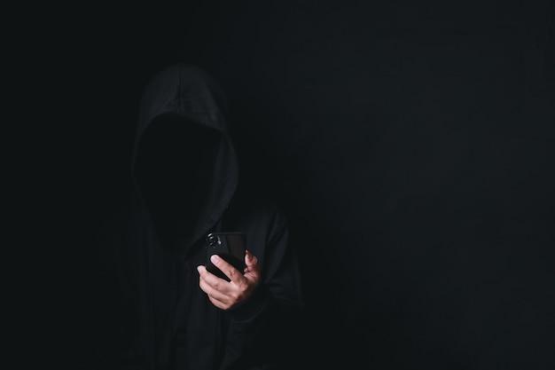 フード付きのスマートフォンで危険な匿名のハッカー男 Premium写真