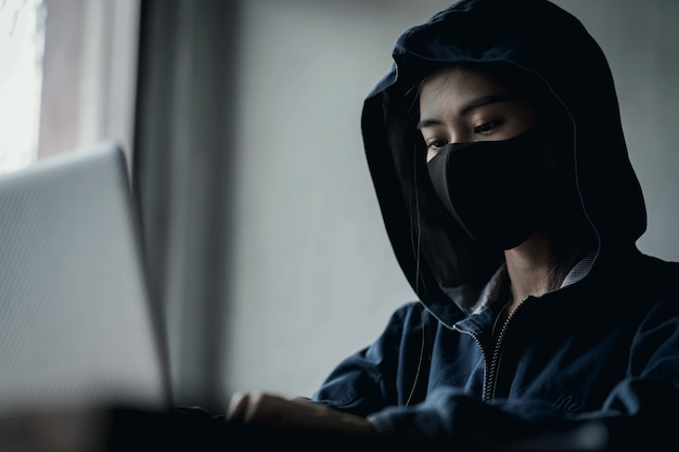 Dangerous hooded hacker using computer, hacking the data Premium Photo